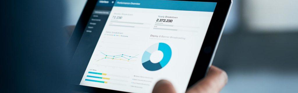 La mano de un hombre sosteniendo una tableta con los paneles de una empresa data-driven