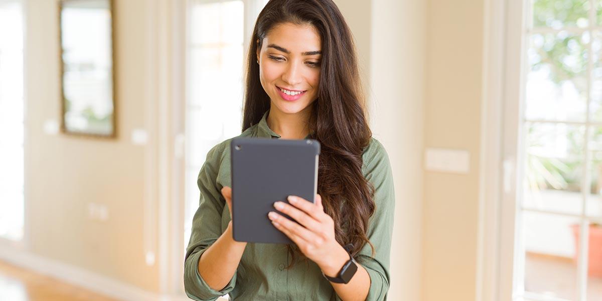 Mujer joven aprendiendo en una tableta cómo gestionar la contabilidad de su empresa desde cualquier dispositivo