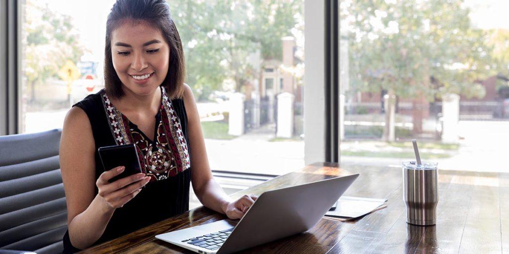 Joven emprendedora utilizando su teléfono inteligente y software personalizado en un entorno de trabajo remoto