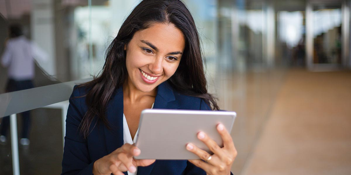Mujer de negocios viendo las condiciones, beneficiarios y montos de Programa PAE-Mype en una tableta