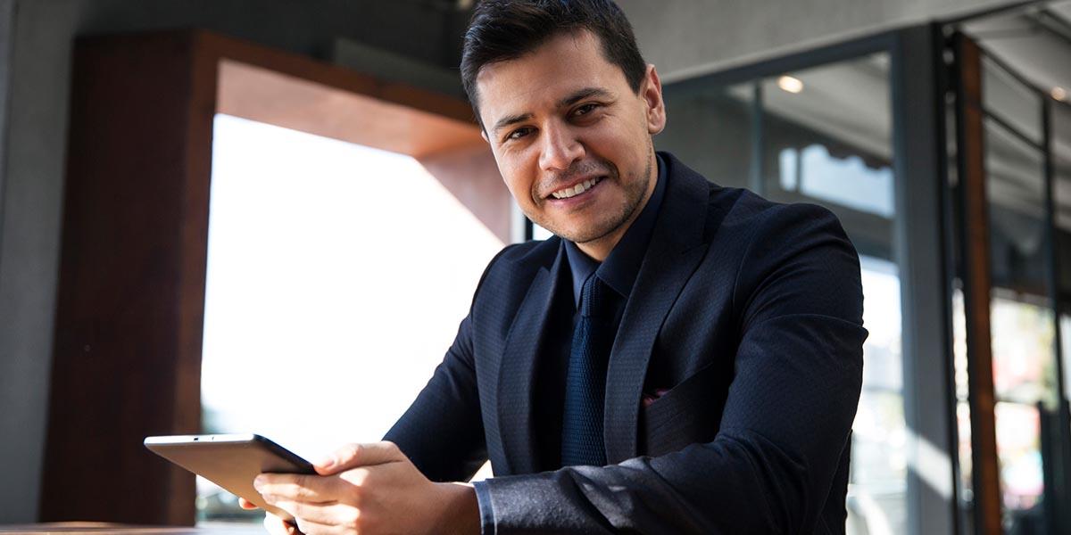 Hombre de negocios sonriendo a la cámara mientras consulta el Subsidio a la planilla en tableta
